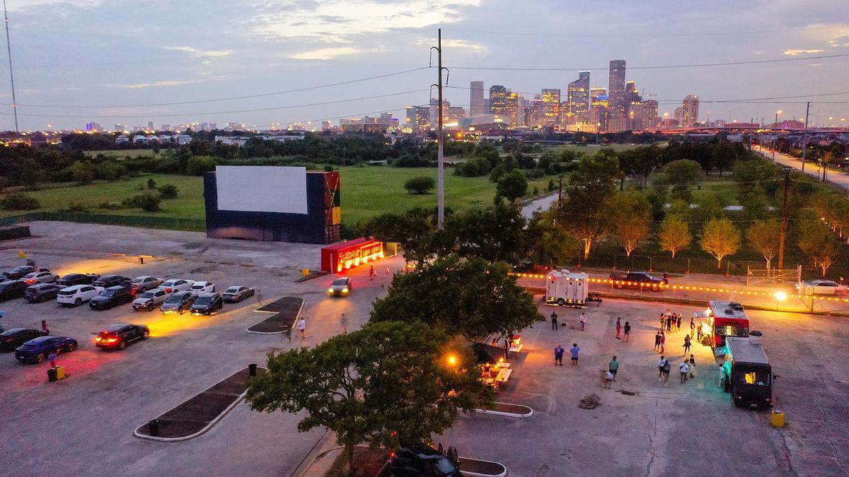 a drone view of a large drive-in screen with cars parked in front. people mingling outside a food truck on the right, and a sunset view of Houston's skyline in the background