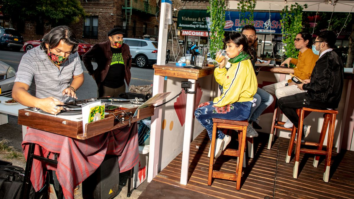 Six people in an outdoor seating area. Four sit on stools, one wearing a mask. One man in a mask plays records at a DJ stand. One man in a mask stands by him.