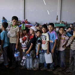 In this Friday, Sept. 7, 2012, photo, Syrians, who fled their homes due to fighting between the Syrian army and the Rebels, line up to collect water from a tanker, as they take refuge at the Bab Al-Salameh border crossing, in hopes of entering one of the refugee camps in Turkey, near the Syrian town of Azaz. The days are still hot across the fertile plains of northern Syria, but at night there is a hint of a chill an ominous harbinger of winter's approach and the deepening of the humanitarian crisis gripping a country wracked by civil war.