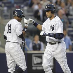 New York Yankees' Derek Jeter, right, is greeted by Curtis Granderson after Jeter hit a home run during the first inning of a baseball game against the Minnesota Twins at Yankee Stadium in New York, Monday, April 16, 2012.