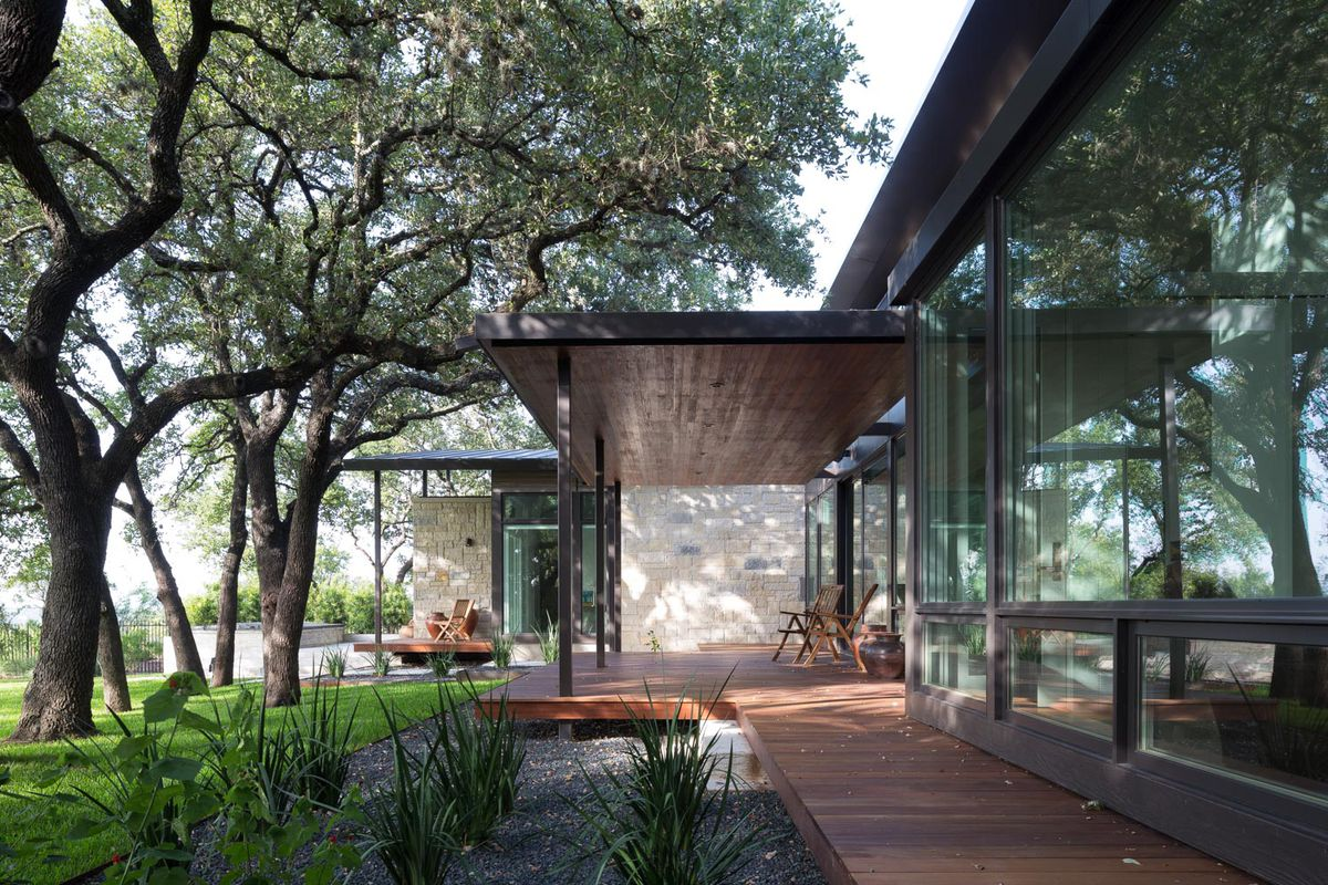 Back of large glass-walled home with deck, flat roof, landscaping, trees