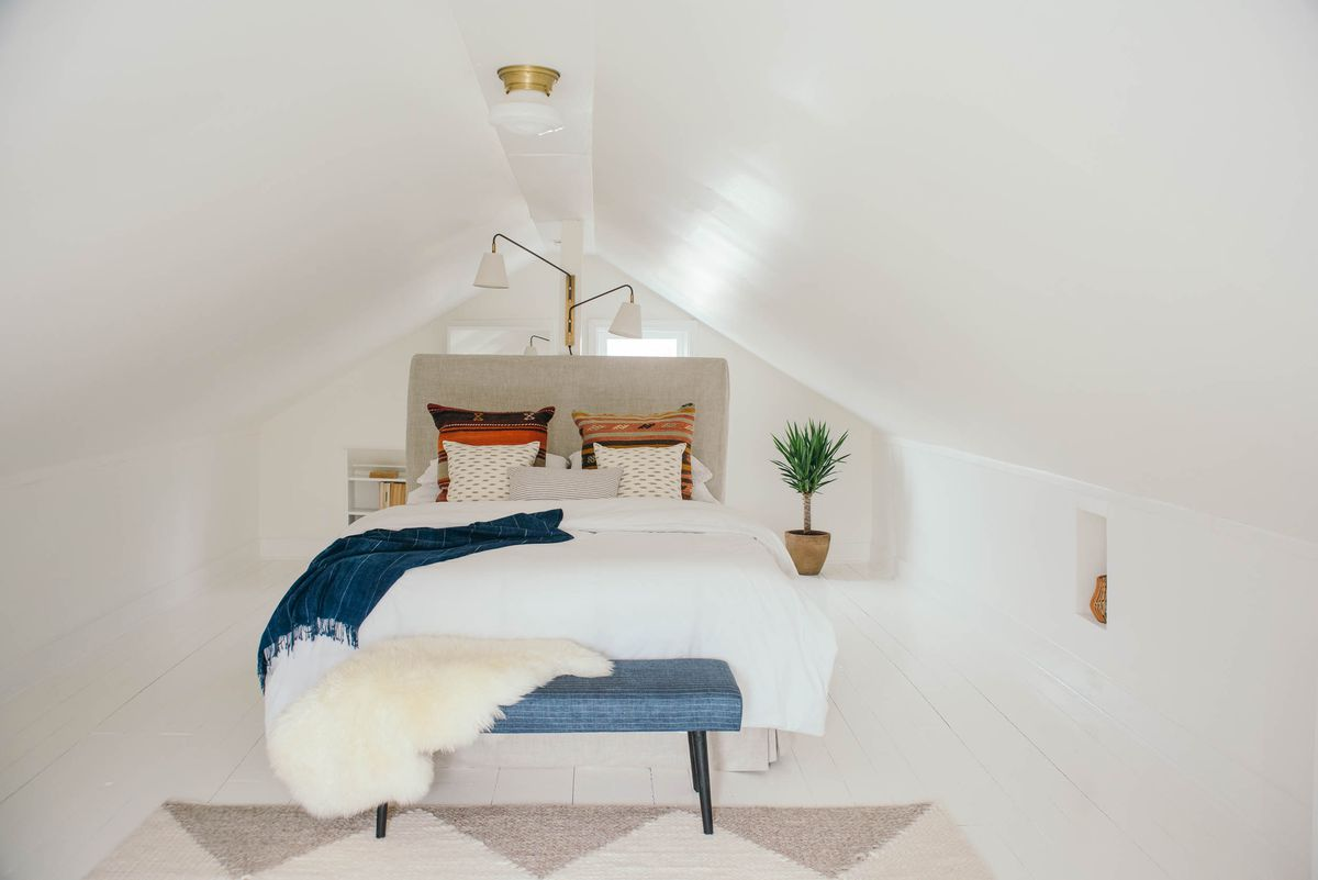 A white attic bedroom with a sloped roof, double bed and potted plant