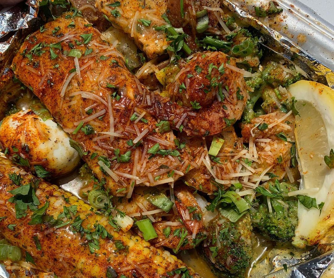 A tin foil-lined takeout container with a piece of salmon, corn on the cob, shrimp, lemon wedge, rice, and herb, all covered in sauce