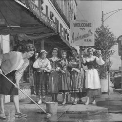 Costumed bell-ringers look on as a shop owner re-enacts the traditional neighborhood sidewalk scrubbing along Clark Street in August 1964.  Sun-Times archives