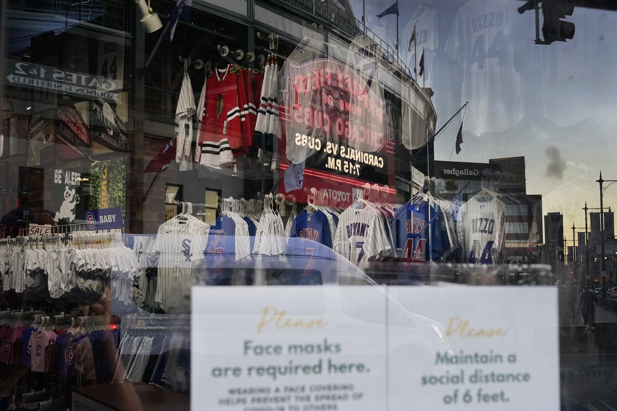 The Wrigley Field marquee is reflected in the window of the Sports World apparel store.