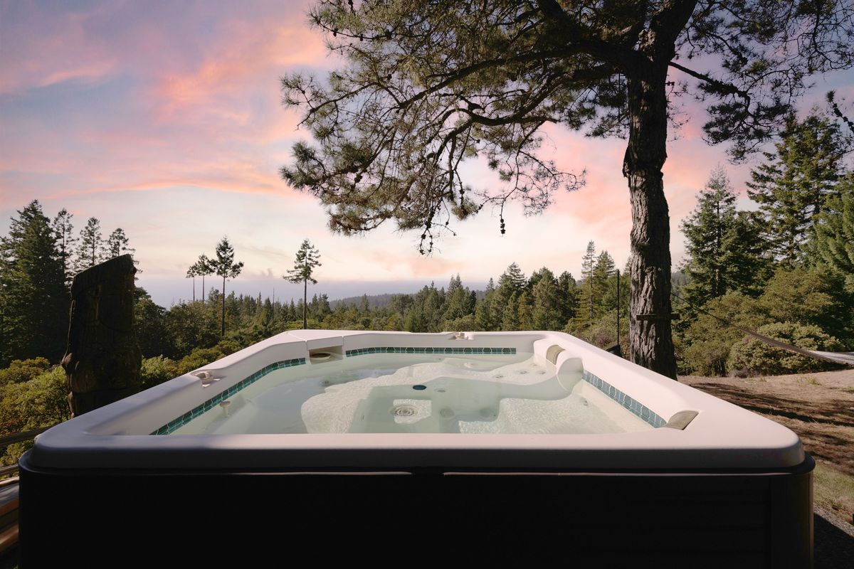 A hot tub overlooking a mountain sunset.