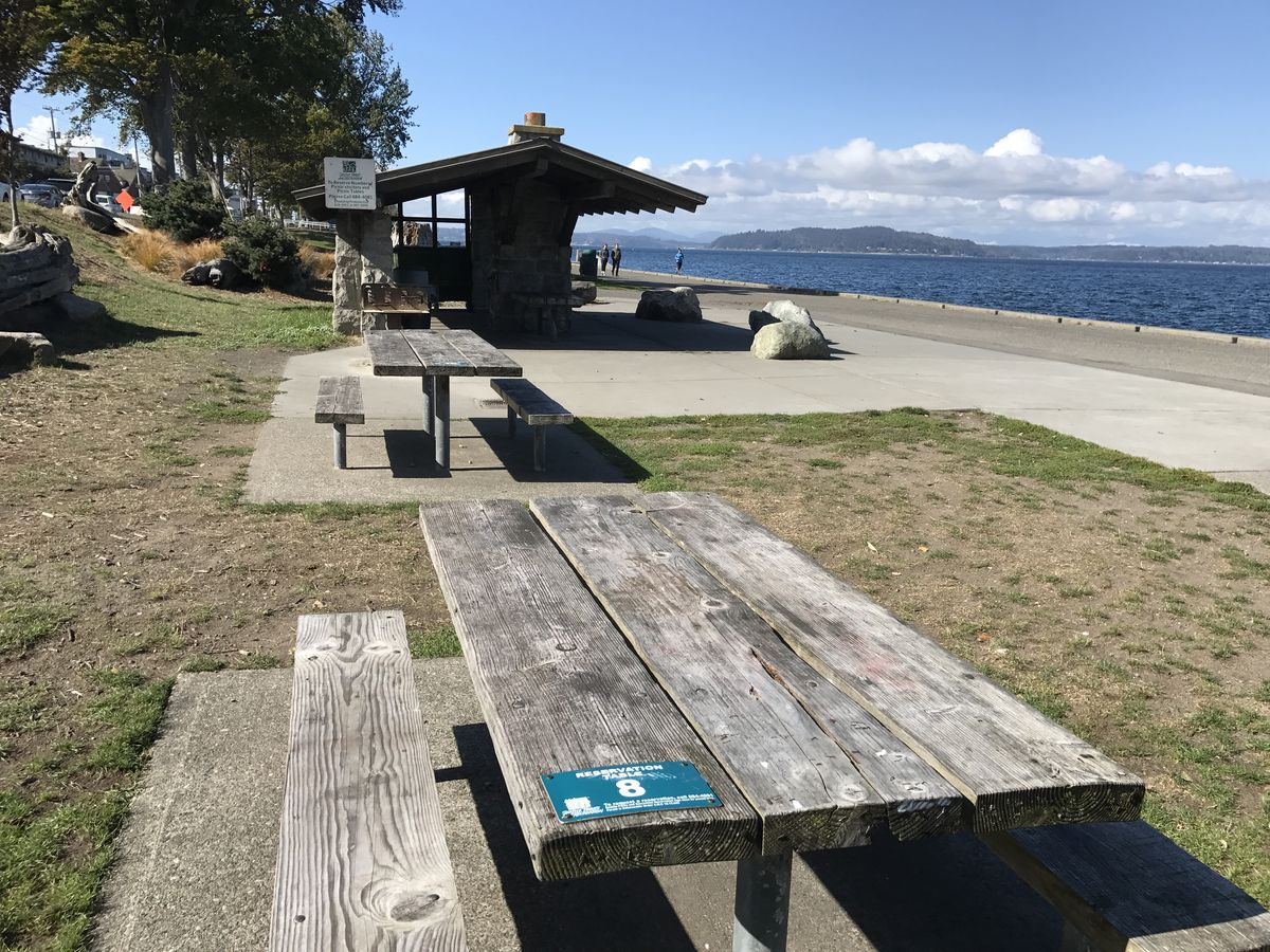 Two picnic tables and a picnic shelter along a beach.