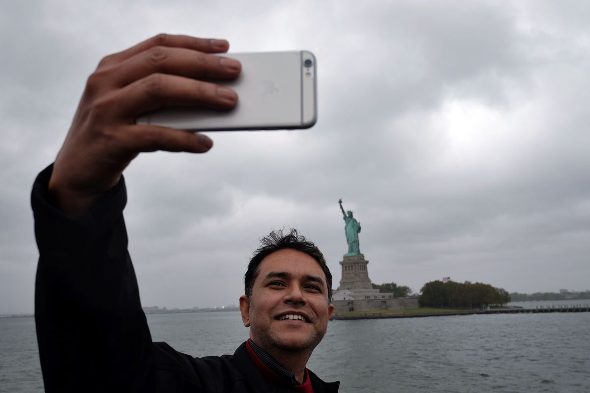 A tourist takes a selfie with the Statue of Liberty.