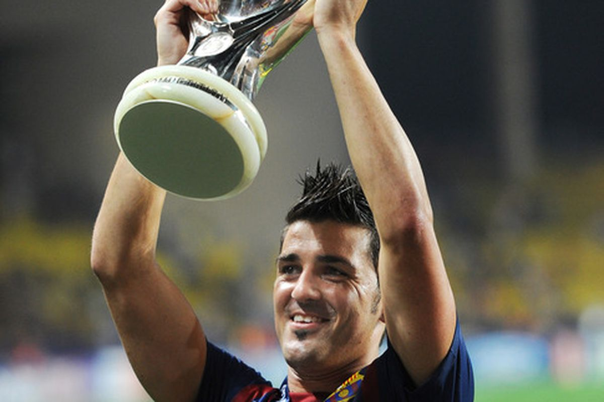 MONACO - AUGUST 26: David Villa of FC Barcelona holds the trophy aloft during the UEFA Super Cup match between FC Barcelona and FC Porto at Louis II Stadium on August 26, 2011 in Monaco, Monaco.  (Photo by Jasper Juinen/Getty Images)