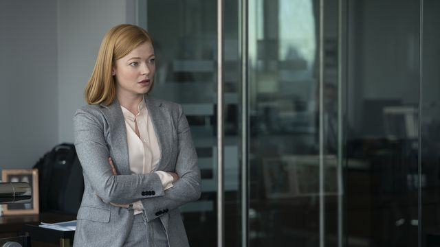 Shiv (Sarah Snook) stands with her arms crossed.