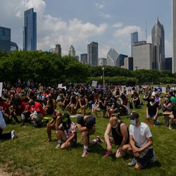 People take a knee in Grant Park during a march that commemorates Juneteenth and George Floyd on June 19, 2020.