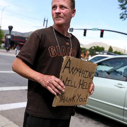 Jessie Cone flies a sign on 400 South in Salt Lake City on Friday, May 1, 2015. A Utah Policy poll finds 2/3 of Salt Lake City residents think panhandling should be illegal. Cone believes that there would be a rise in shoplifting if panhandling becomes fully illegal. Cone has been on his own since his 13th birthday, when he had had enough of his stepfather's abuse.