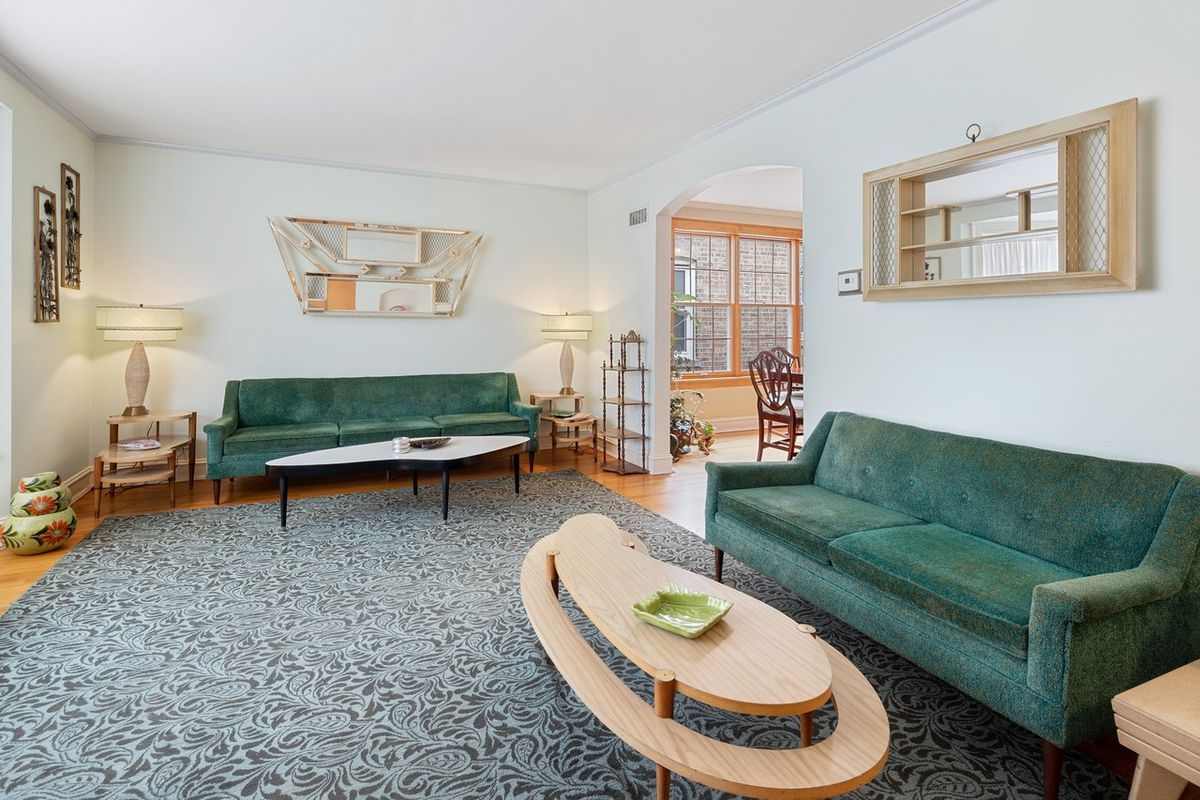 A large living room with two green couches, wood coffee tables, and a large bay window just out of view.