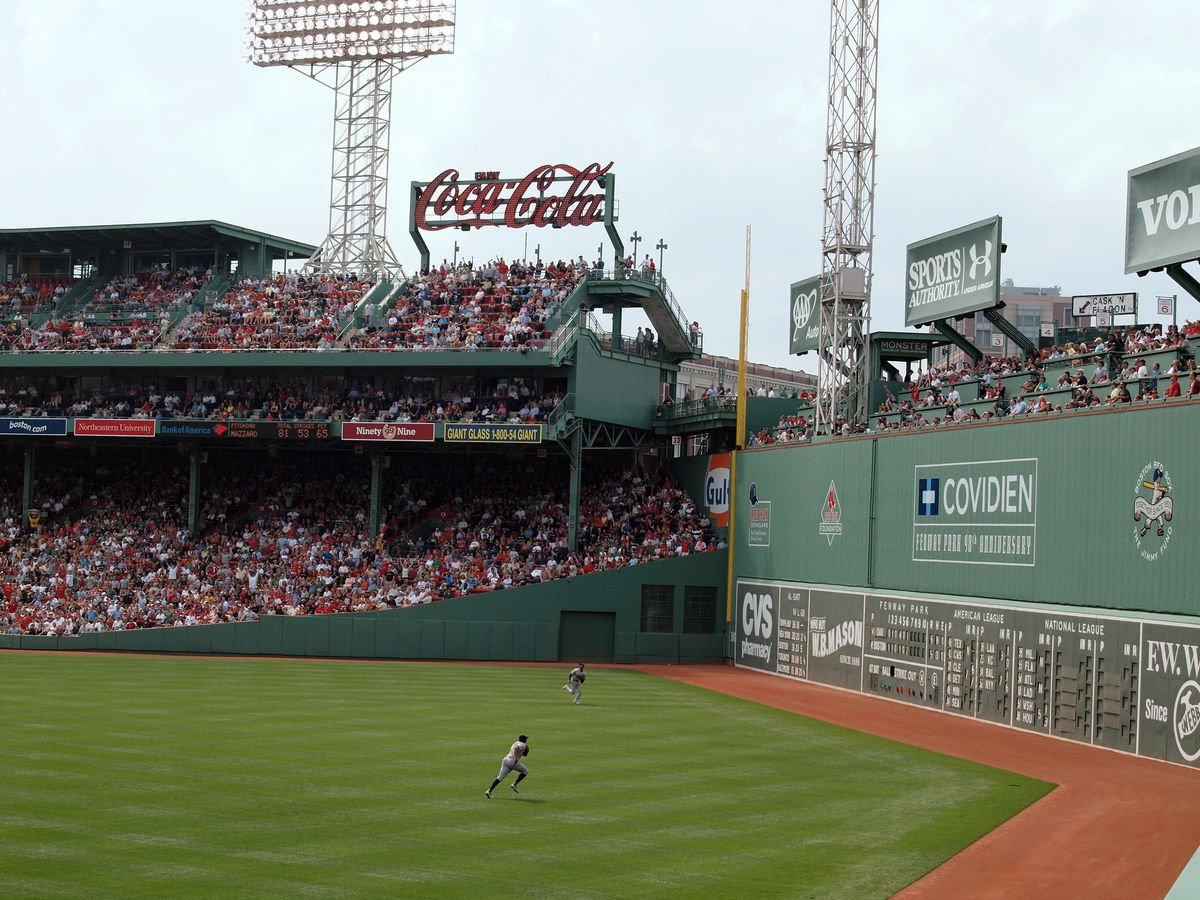 Baseball players running toward a tall, green wall.