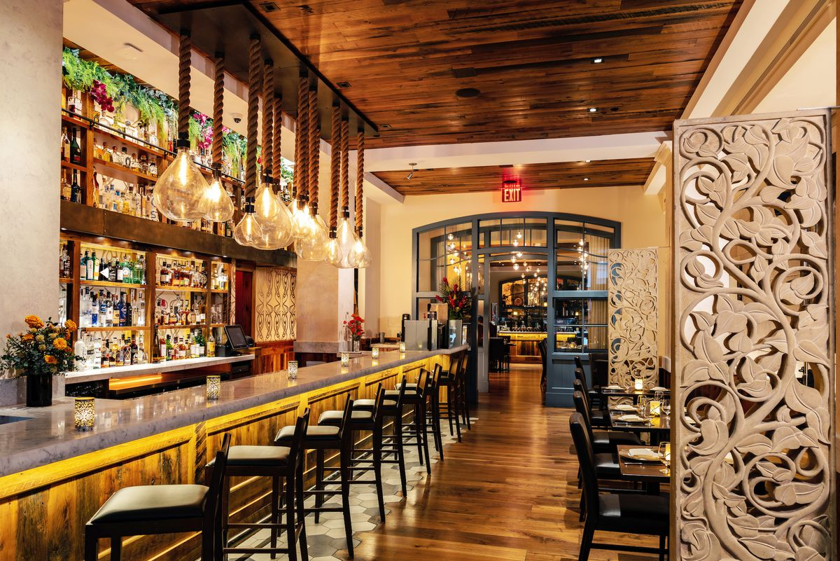 An ornate dining room with custom light fixtures, dark wood ceilings and a long bar with high-top seating