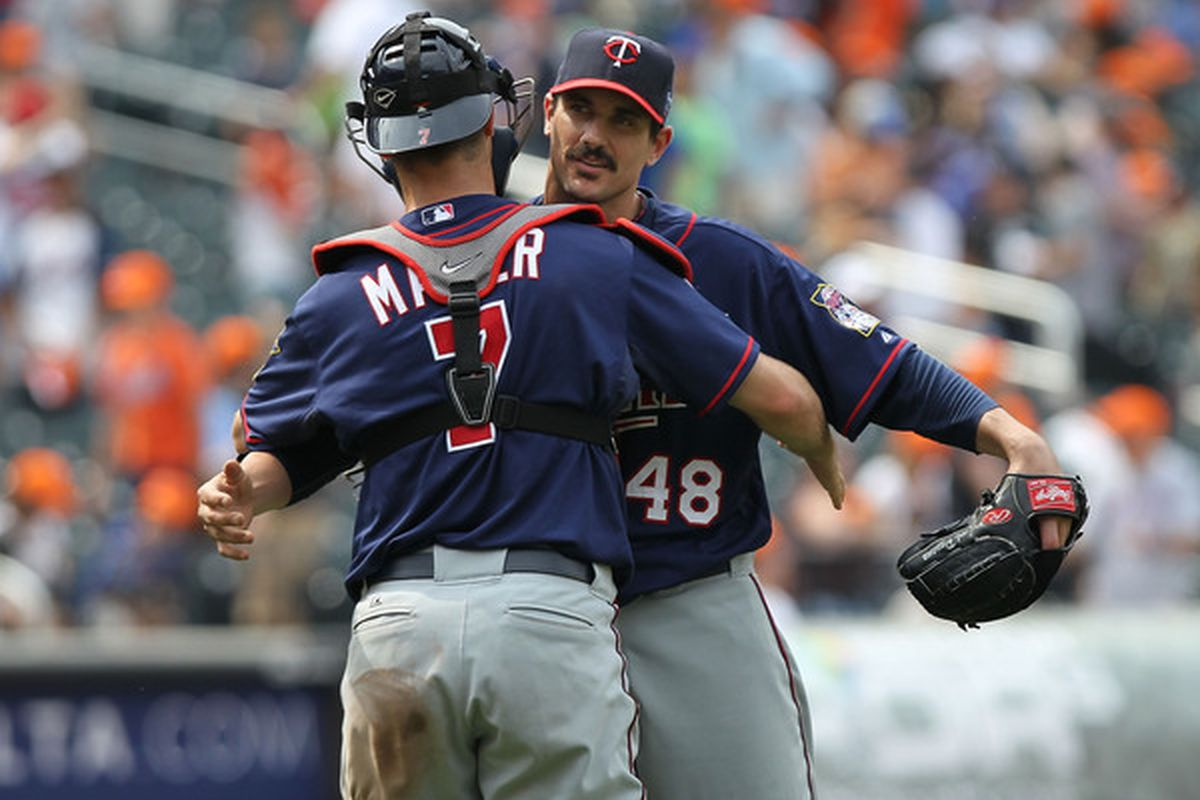 NEW YORK - JUNE 26:  Carl Pavano #48 of the Minnesota Twins hugs catcher Joe Mauer #7 against the New York Mets at Citi Field on June 26, 2010 in the Flushing neighborhood of the Queens borough of New York City.  (Photo by Nick Laham/Getty Images)