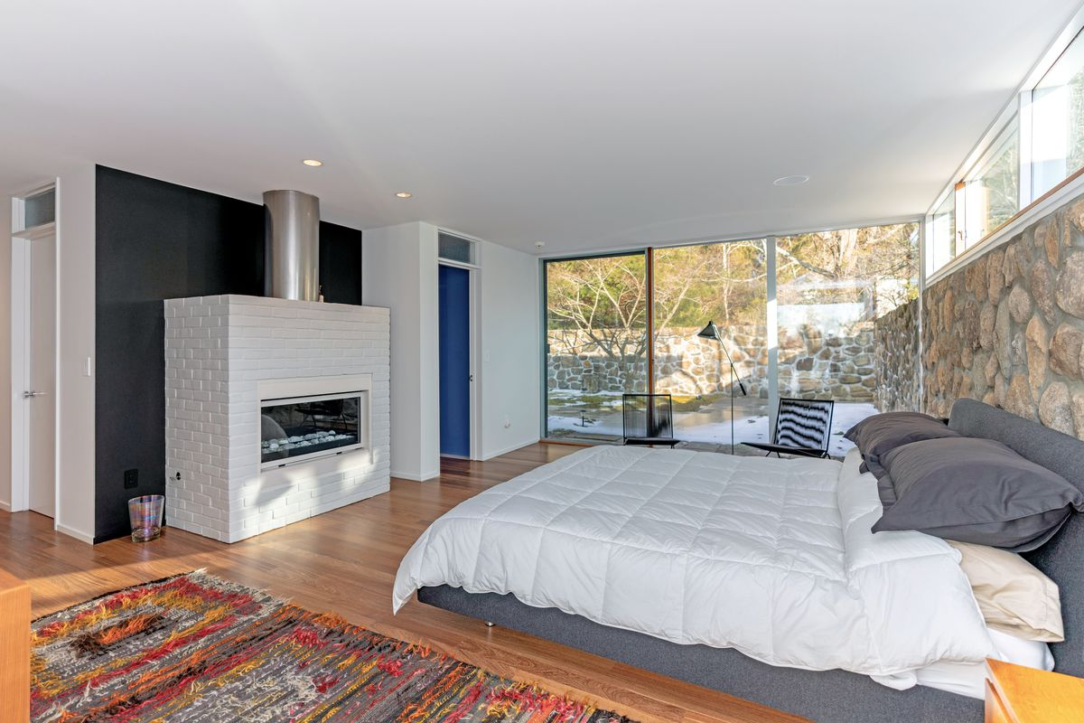 A bedroom has a large white and gray bed facing a white brick fireplace.