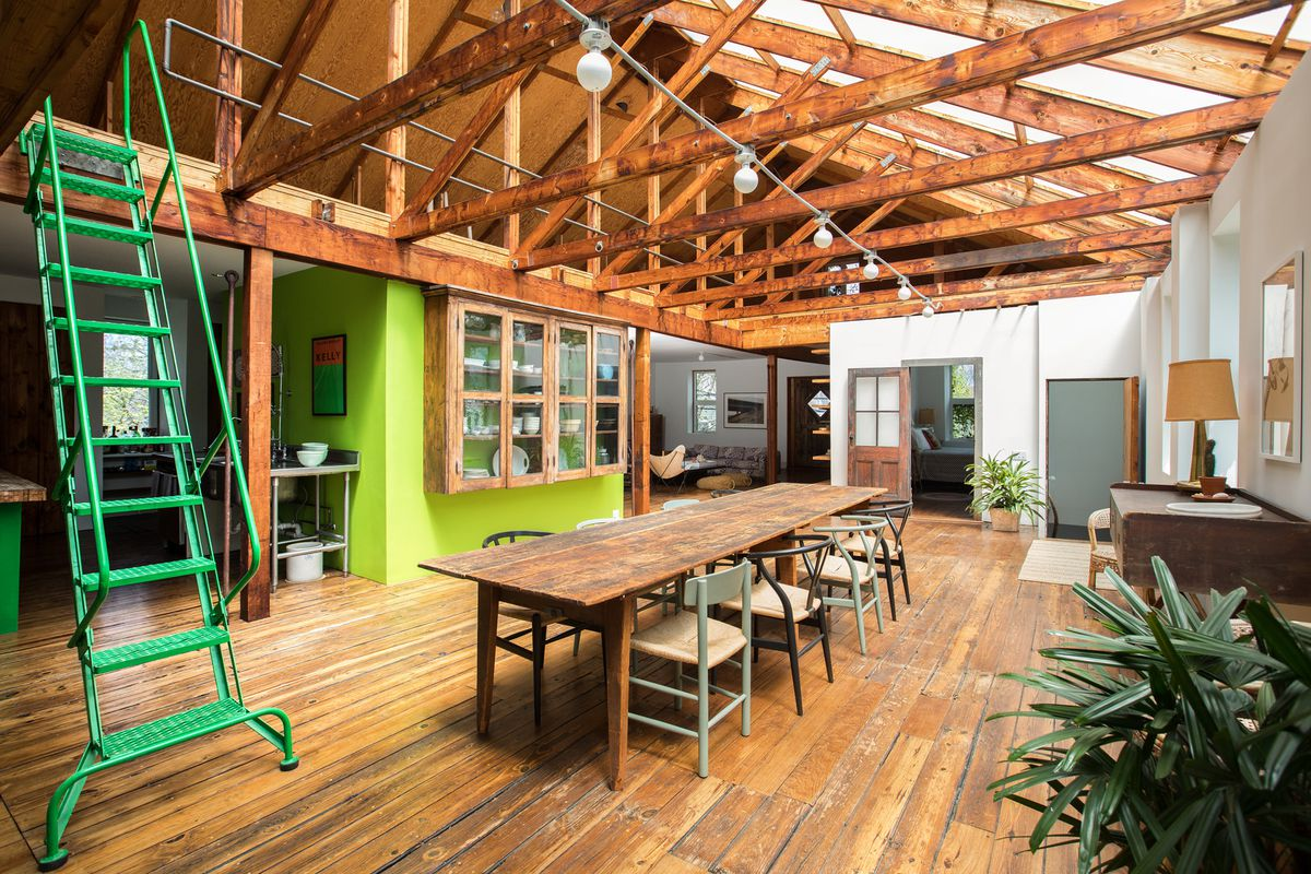 A rafted open living area has a wooden table, wood floors, and a bright green staircase.