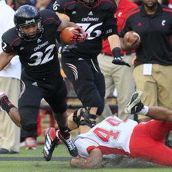 Cincinnati running back George Winn (32) is tackled by Delaware State defensive back Davon Moore (44) during the first half of an NCAA college football game, Saturday, Sept. 15, 2012, in Cincinnati.