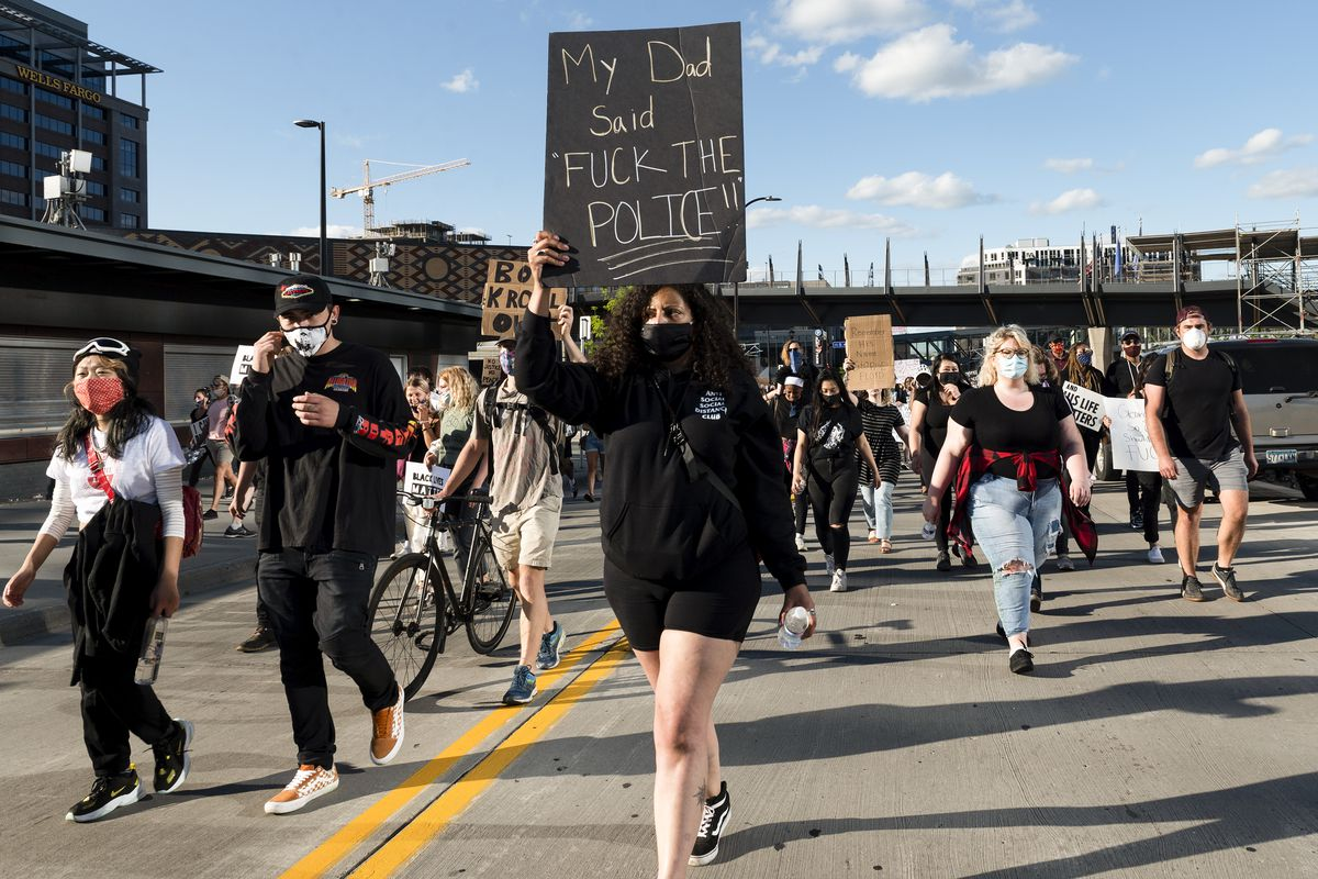 "A socially distance group of people march towards the photographer. At their forefront is a woman in black, with a black mask, and a black sign that reads: ""My Dad said, 'Fuck the police!!'"""