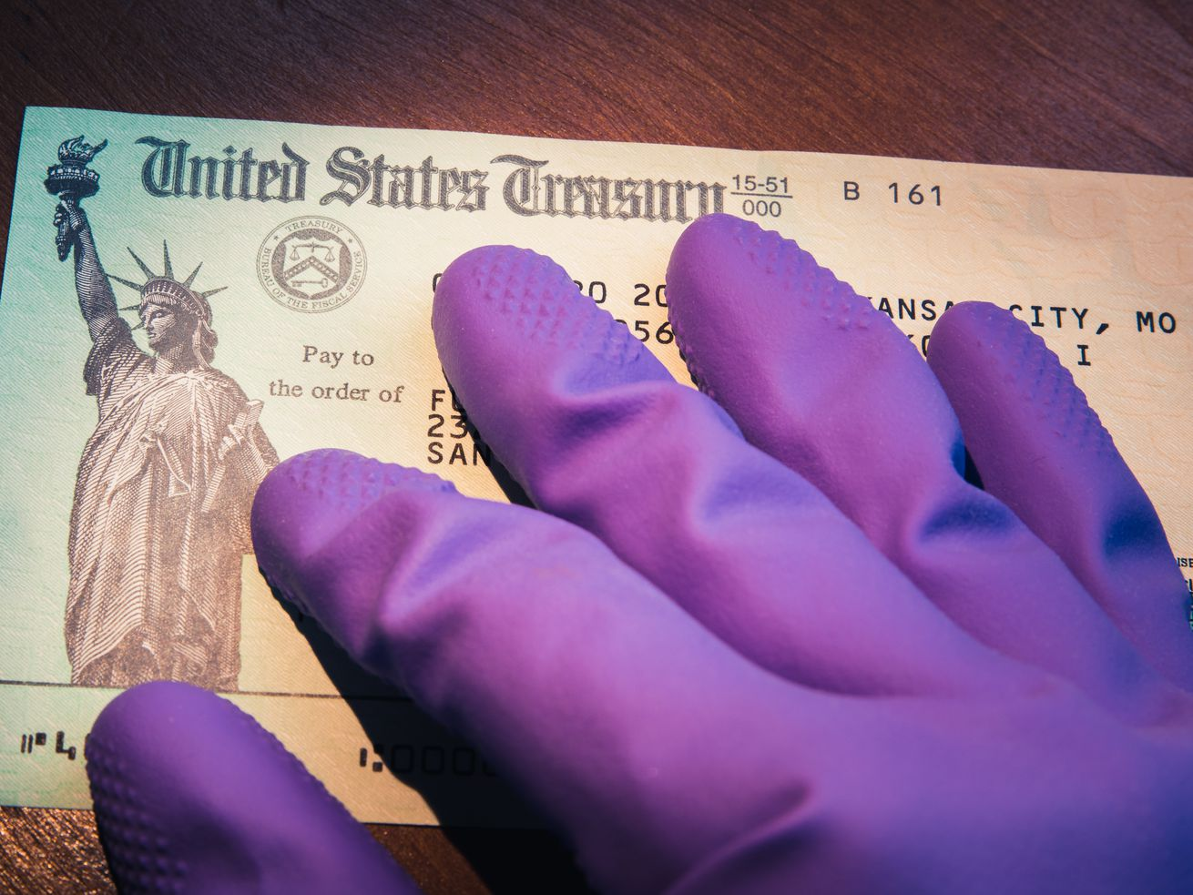 Gloved hand touching a tax return Treasury check to symbolize the COVID pandemic economic impact.