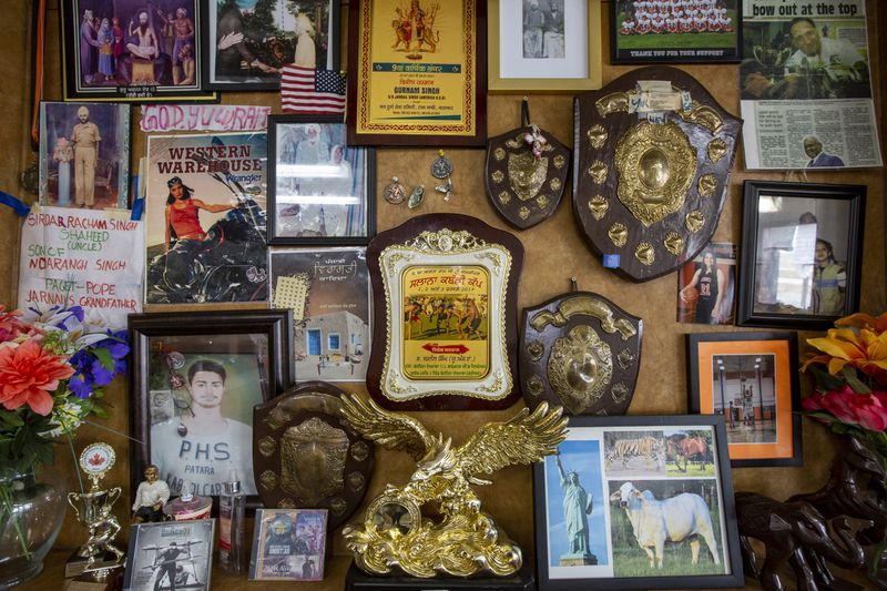 A jumble of plaques, framed photos, and other ephemera on a wall.