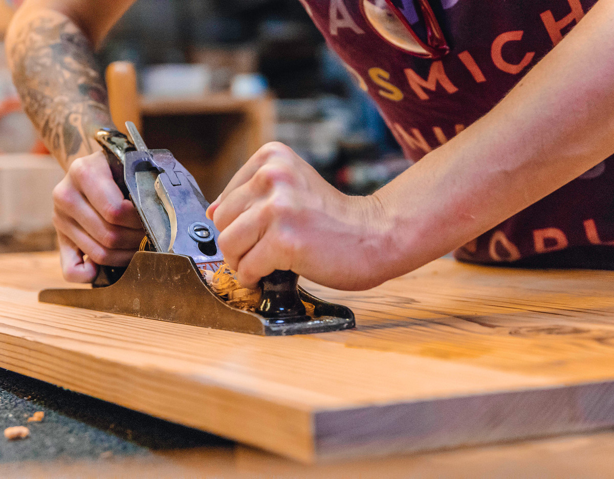 A person operates a tool on a block of wood in a workshop.
