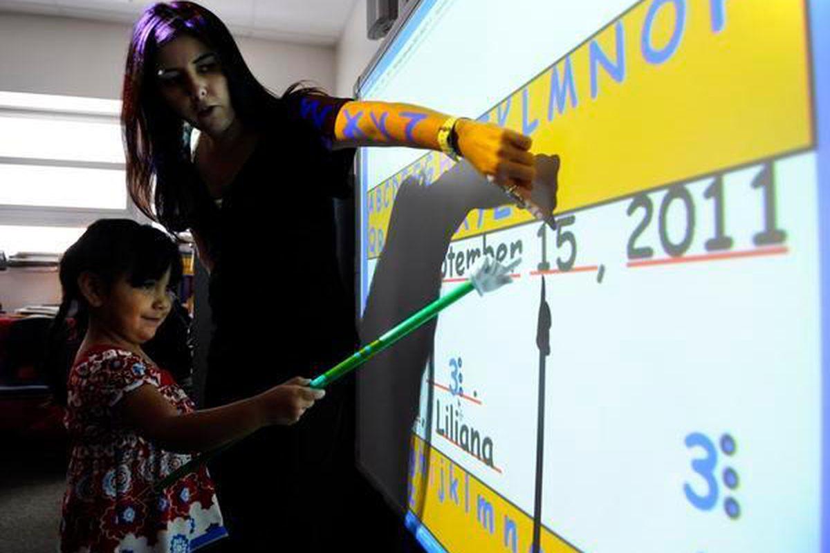 Teacher Jonell Tafoya works with student Liliana Lucero in 2011 at Gust Elementary in southwest Denver.