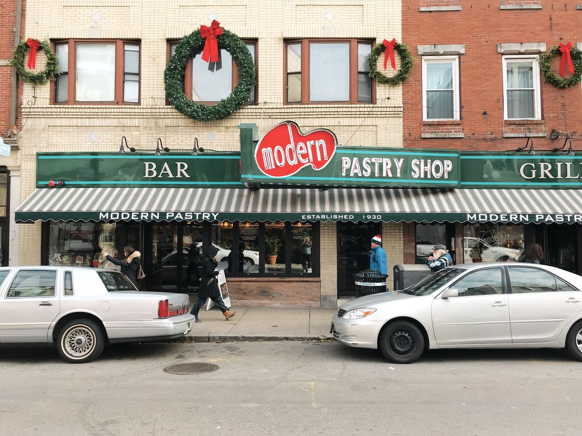 The exterior of Modern Pastry Shop in Boston's North End features a red and green sign and a green and white striped awning. Large Christmas wreaths hang above the sign in this photo.