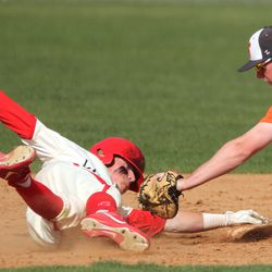 American Fork's Dax Newman gets back to second base after hitting in three RBIs and getting a double as Skyridge's Colby Carter tries to tag him in American Fork on Friday, April 30, 2021.
