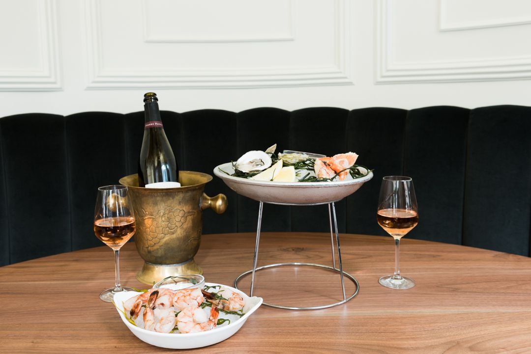 Two raw bars on ice, a bottle of Champagne on ice, and two glasses of wine sit on a wood table
