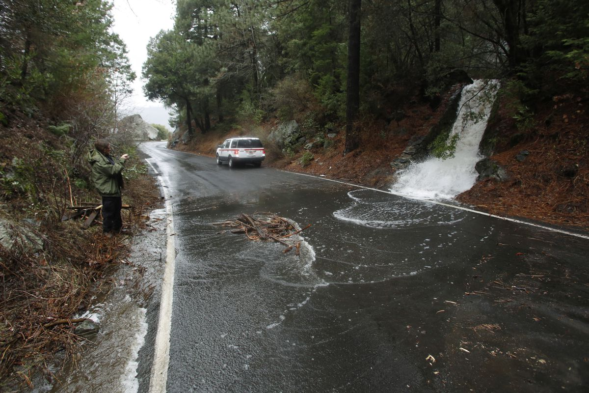 A waterfall heads across the road near the Merced River in a closed off Yosemite National Park, Calif., Sunday, Jan. 7, 2016.