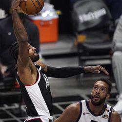 Los Angeles Clippers guard Paul George, left, dunks as Utah Jazz center Rudy Gobert watches during the second half of Game 3 of a second-round NBA basketball playoff series Saturday, June 12, 2021, in Los Angeles.