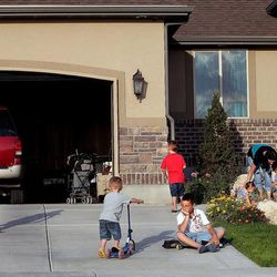 The Hyde family, Davis, left, Laryn, Will, Gabe, Dax, twins Hazel and Hattie, mom Camilla and father Trent, plays outside at their home in Syracuse on Thursday, Aug. 1, 2013.