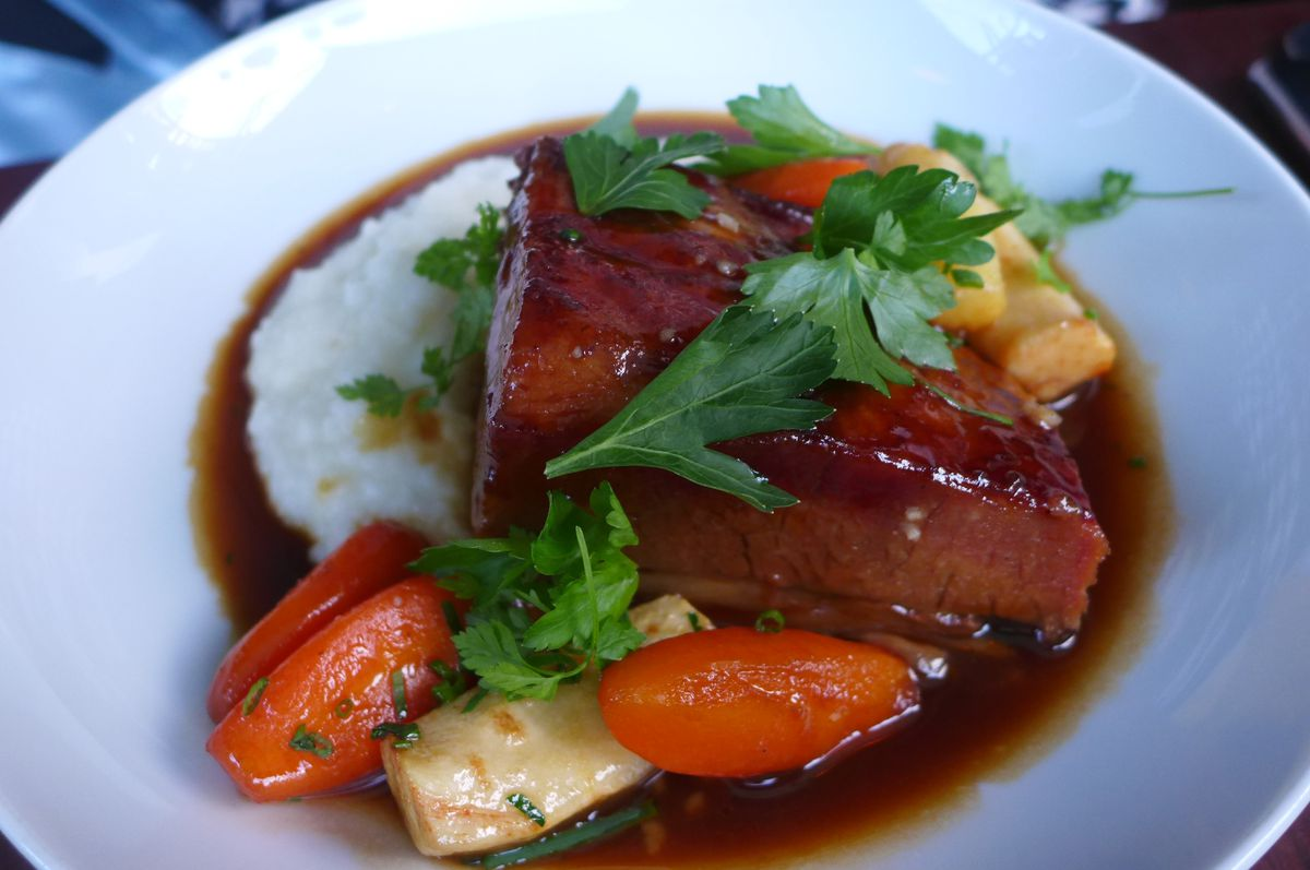 A thick wedge of meat covered with a transparent reddish demiglace, with vegetables strewn around.