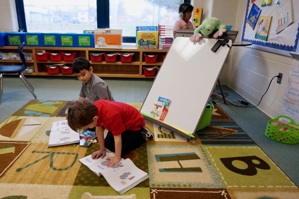 Two children read picture books in a classroom.