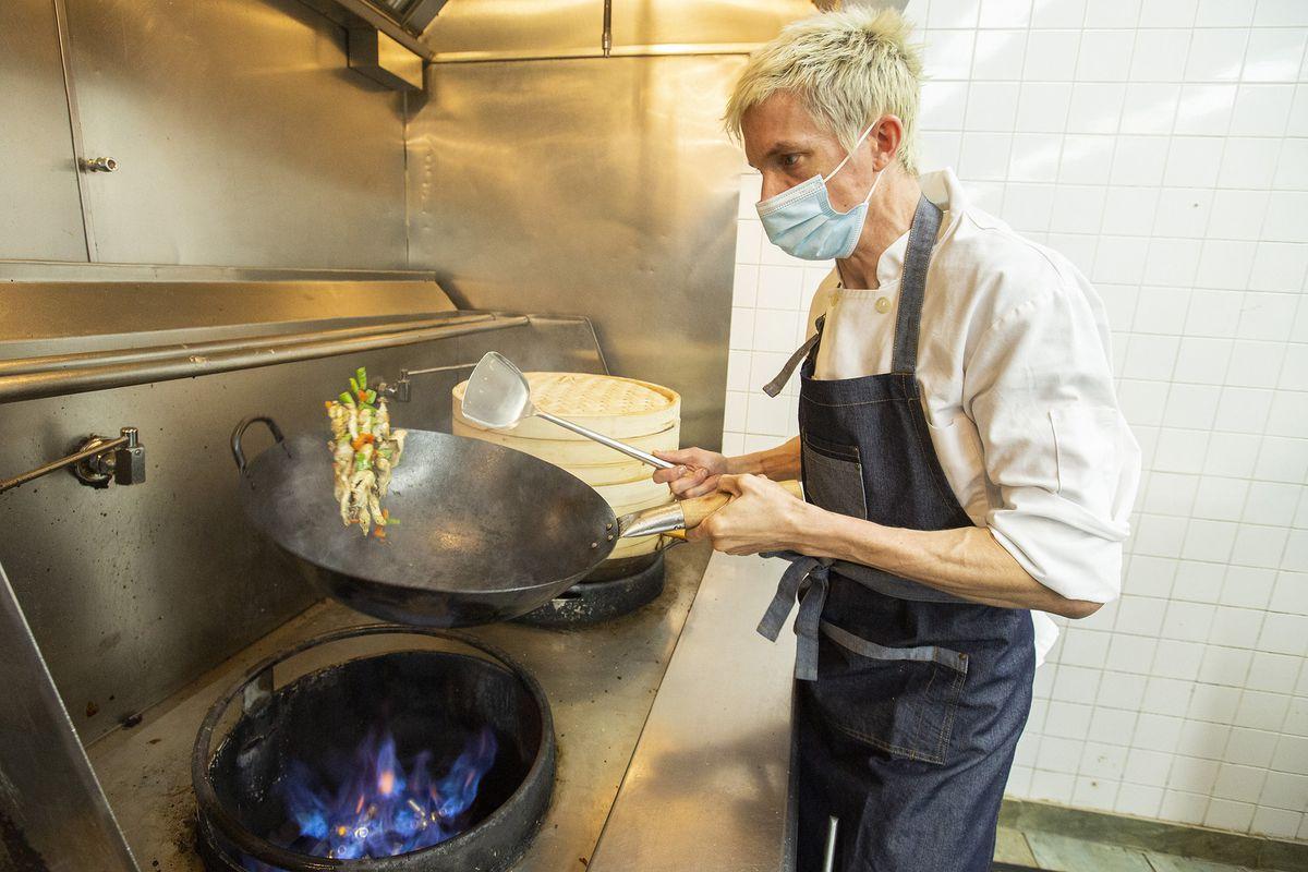 Kevin Schuder tossing vegetables in a wok