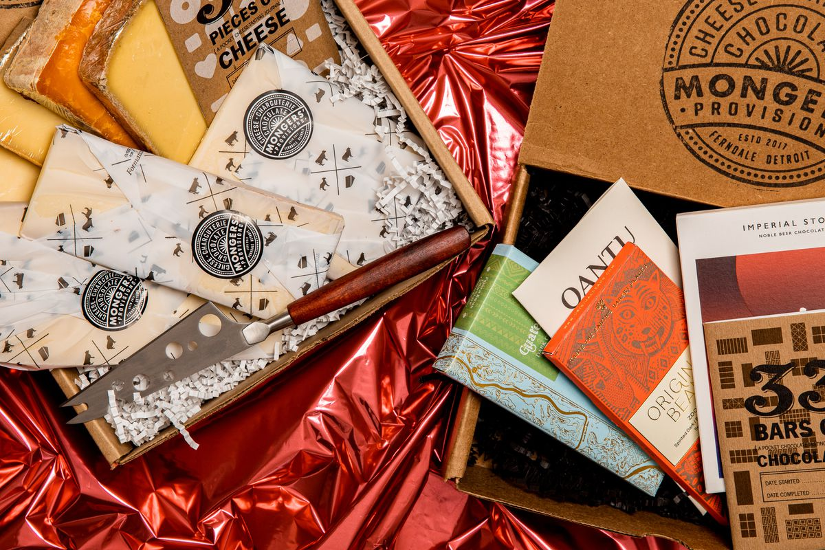 Cheese wrapped in Mongers Provisions paper with a cheese knife and a separate box filled with assorted chocolate bars.