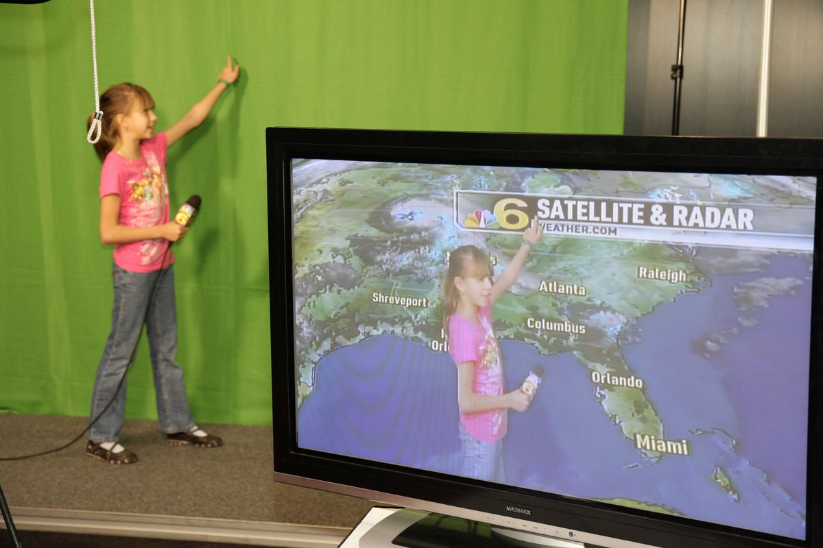A girl pretending to do the weather on Channel 6 at the Health and Fitness Expo