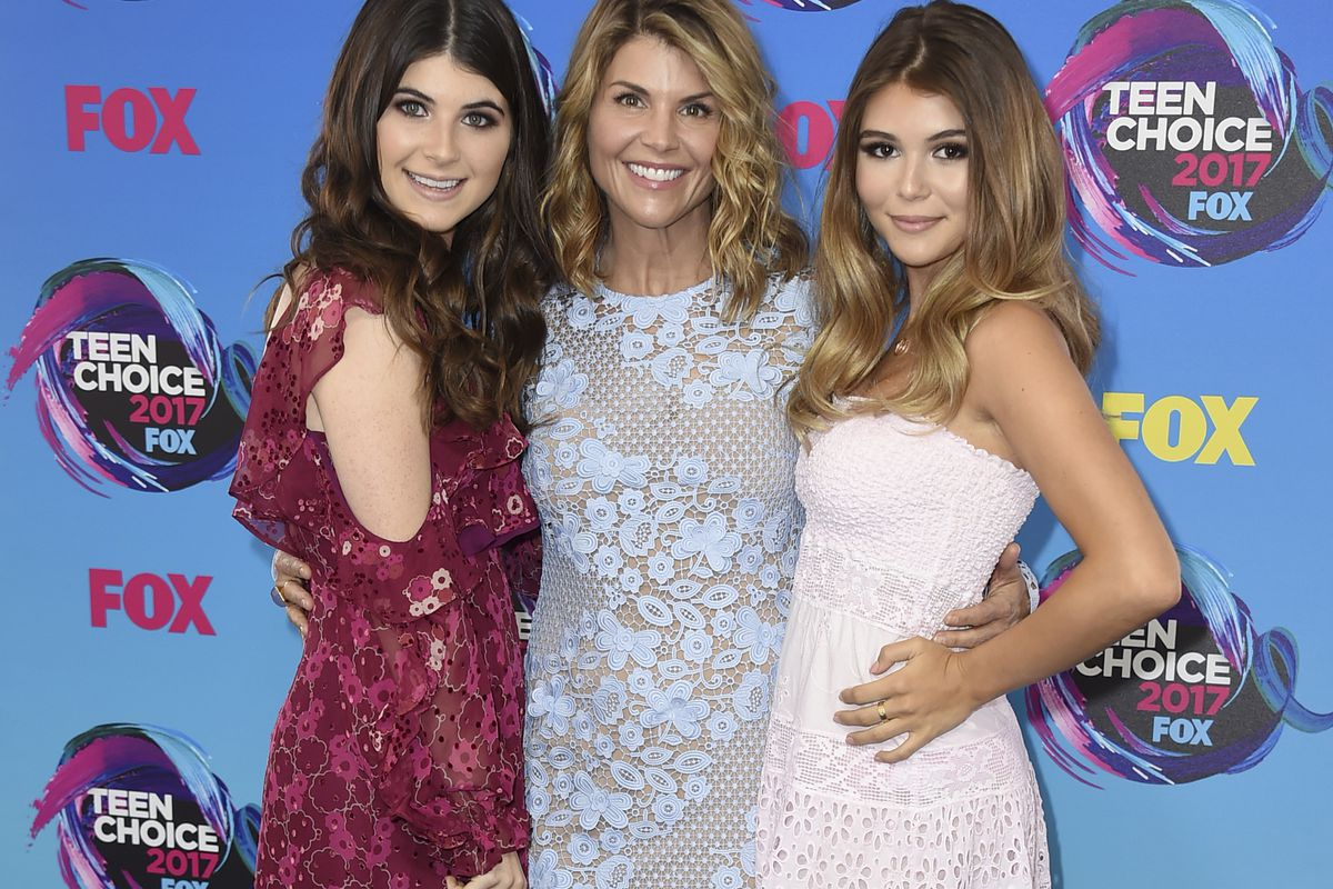 In this Aug. 13, 2017 file photo, actress Lori Loughlin, center, poses with her daughters Bella, left, and Olivia Jade at the Teen Choice Awards in Los Angeles. The FBI says actress Lori Loughlin has been taken into custody in connection with a scheme in
