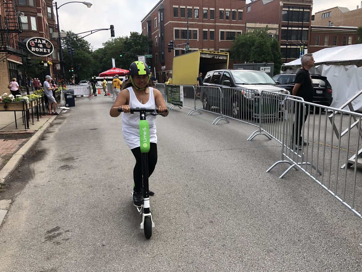 Marnie Pilgrim, who is part of Lime's Chicago operations, demonstrates one of the firm's electric scooters on Sunday.   Mitch Dudek/Sun-Times