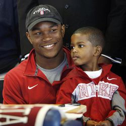 Heritage Hall's Barry J. Sanders smiles as he holds his brother Terrance Johnson, 4, during national signing day at Heritage Hall in Oklahoma City, Wednesday, Feb. 1, 2012. Sanders is announced he planned to attend Stanford.
