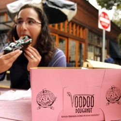 Jennie Myren, who is from Iowa and spending her honeymoon in Portland, enjoys the signature doughnut shaped like a voodoo doll with a pretzel stick stake through its' heart outside the famous Voodoo Doughnuts shop in downtown Portland, Ore., Wednesday, Sept. 19, 2012. Researchers at Portland State University found that the Portland atmosphere and culture is a magnet for the young and college educated, even though a disproportionate share of them are working in part-time jobs or positions that don't require a college degree.
