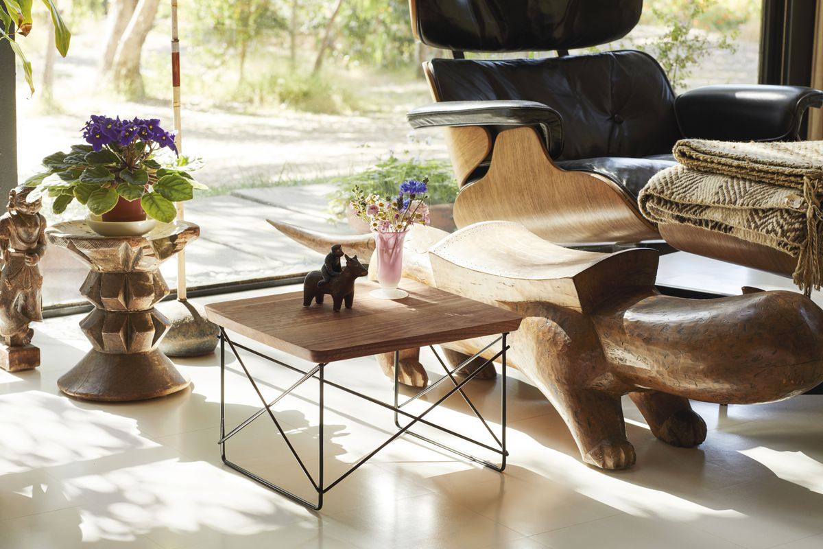 A low wood-topped table sits in a bright room, next to wooden sculpture depicting four-legged creation and a leather lounge chair. A plant and a figurine of a person riding a horse stand on the table.