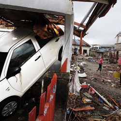 A car is upended in its parking stall as people walk the debris strewn streets in Tacloban, Friday, Nov. 22, 2013.