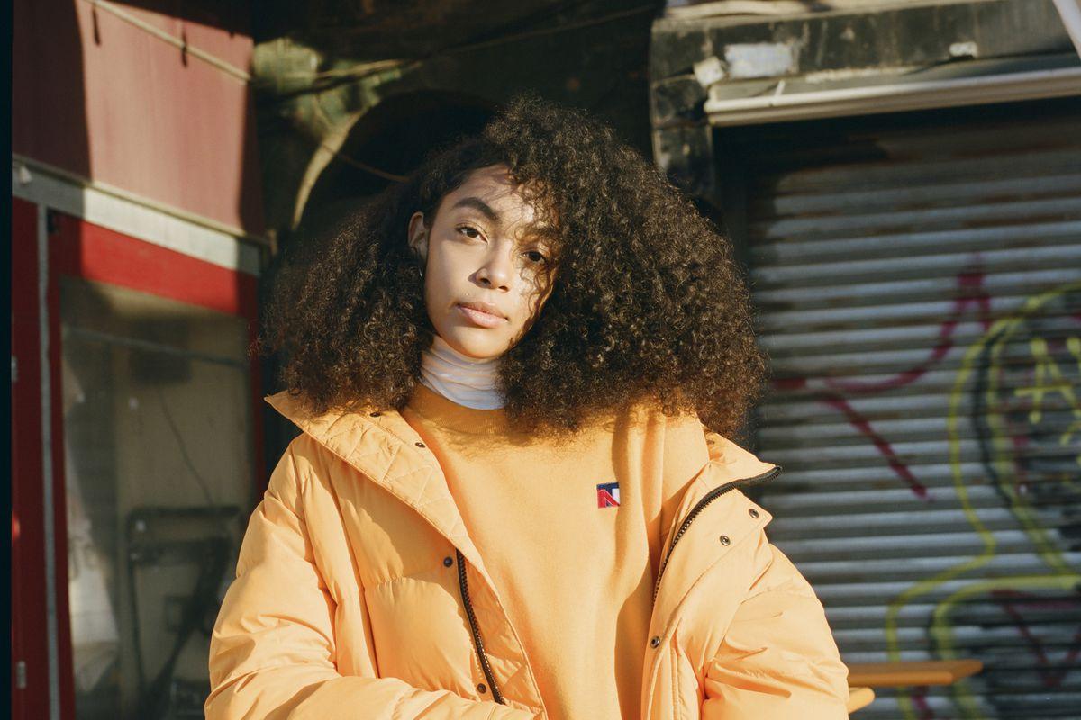A woman in an orange puffer coat