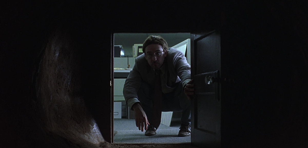 John Cusack peeing into a tiny door in 'Being John Malkovich'