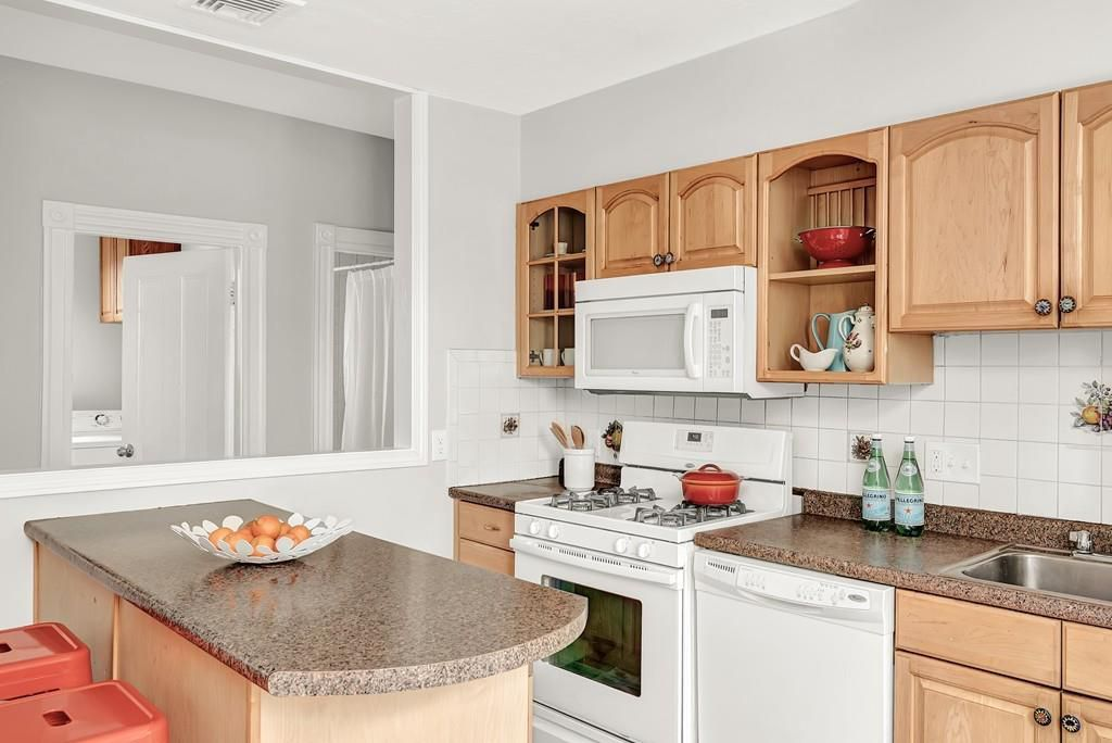A snug kitchen with an island and a run of cabinetry and counters.