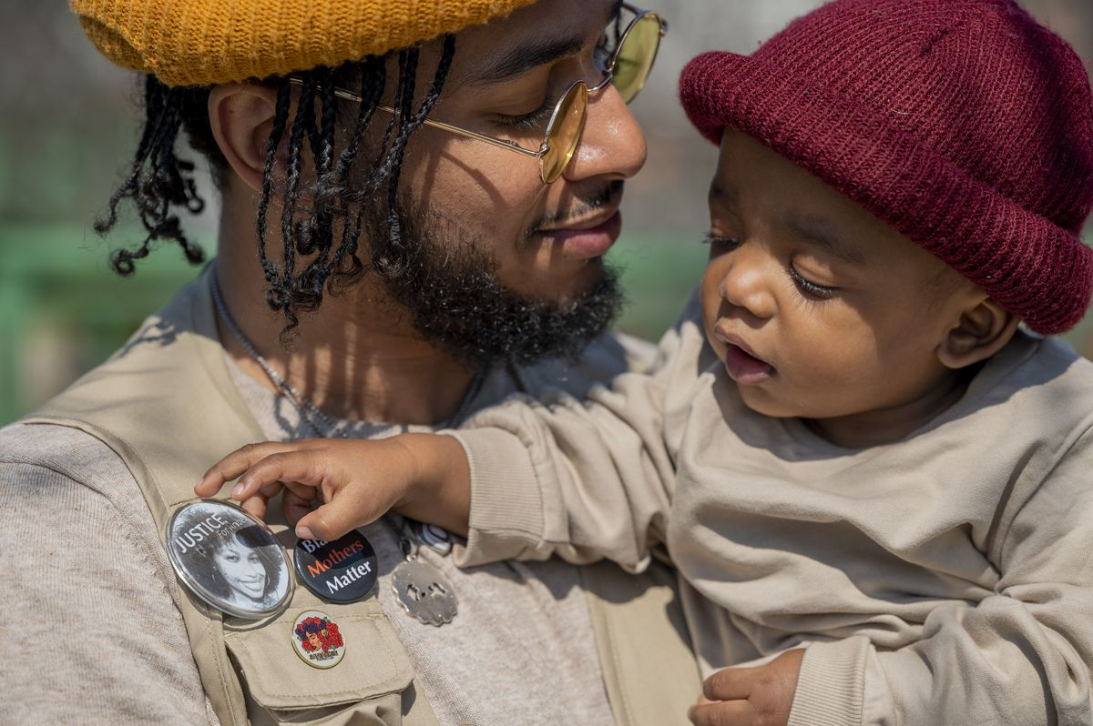 """Bruce McIntyre holds his son, Elias, as the young boy reaches for a button of his mother that reads """"Justice For Amber."""""""