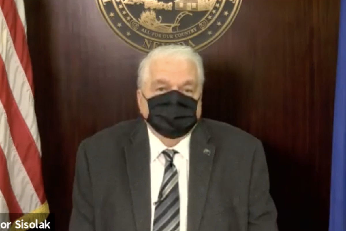 A man wears a suit and a mask with the American flag on the left